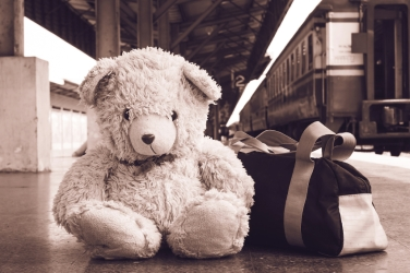 vintage tone, teddy bear sitting alone at Railway Platform